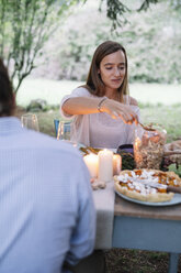 Couple having a romantic candlelight meal in garden - ALBF00736