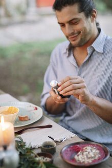 Man opening a bottle of sparkling wine at garden table - ALBF00739