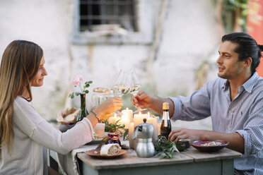 Couple having a romantic candlelight meal clinking wine glasses - ALBF00742