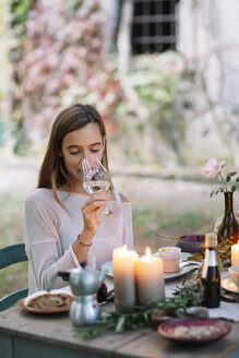 Woman tasting glass of wine at garden table - ALBF00745