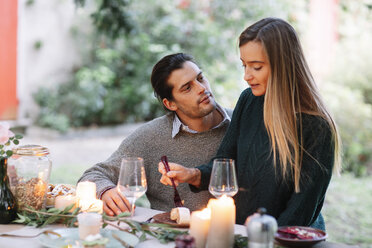 Romantic couple having a candlelight meal at garden table - ALBF00748