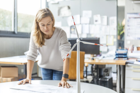 Woman in office working on plan with wind turbine model on table - TCF06010