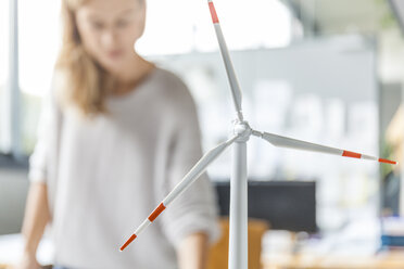 Wind turbine model and woman in background in office - TCF06013