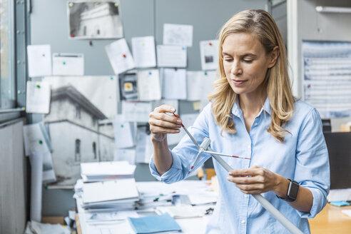 Woman in office working on wind turbine model - TCF06040