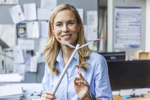 Portrait of smiling woman in office holding wind turbine model - TCF06043