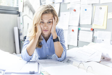 Stressed woman sitting at desk in office surrounded by paperwork - TCF06046