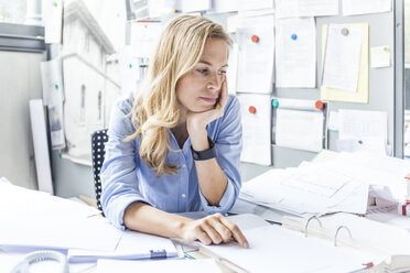 Pensive woman sitting at desk in office surrounded by paperwork - TCF06049