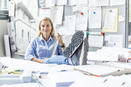Woman relaxing at desk in office surrounded by paperwork - TCF06052