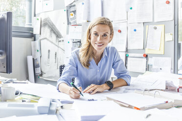Portrait of smiling woman doing paperwork at desk in office - TCF06055