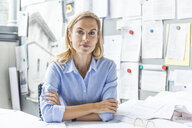 Portrait of confident woman sitting at desk in office surrounded by paperwork - TCF06058