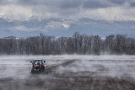 Hokkaido, Tractor seeding a field while it is vaporating from the warm ground - RUNF00307