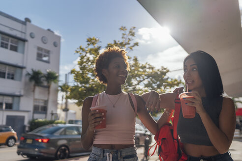 USA, Florida, Miami Beach, two happy female friends having a soft drink in the city - BOYF01163