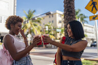 USA, Florida, Miami Beach, two happy female friends having a soft drink in the city - BOYF01169