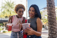 USA, Florida, Miami Beach, two happy female friends with cell phone and soft drink in the city - BOYF01172