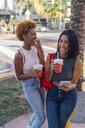 USA, Florida, Miami Beach, two happy female friends with cell phone and soft drink in the city - BOYF01175