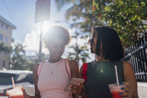 USA, Florida, Miami Beach, two happy female friends with cell phone and soft drink in the city - BOYF01184