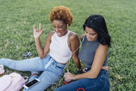 Two happy female friends relaxing in a park listening to music - BOYF01187