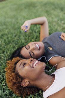 Portrait of two happy female friends relaxing in a park listening to music - BOYF01193