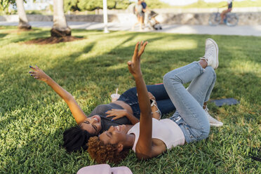 Two happy female friends relaxing in a park listening to music - BOYF01196