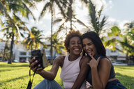 Two happy female friends taking an instant photo in a park - BOYF01202