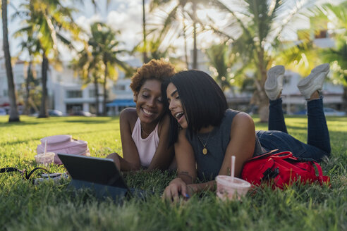 Two happy female friends relaxing in a park using a tablet - BOYF01205