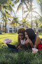 Two happy female friends relaxing in a park using a tablet - BOYF01208
