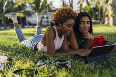 Two female friends relaxing in a park using a tablet - BOYF01211