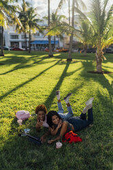 Two happy female friends relaxing in a park using a tablet - BOYF01214