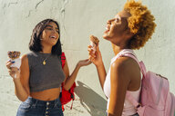 Two happy female friends with ice cream cones at a wall - BOYF01223