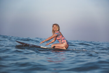 Indonesia, Bali, pregnant woman sitting on surfboard - KNTF02453