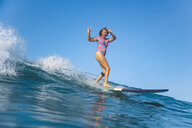 Indonesia, Bali, Batubolong beach, Pregnant woman surfing making sign of the horns - KNTF02456