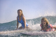 Indonesia, Bali, Batubolong beach, young female surfers on board, splash water - KNTF02459