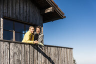 Couple leaning on balcony of a mountain hut, holding map - UUF15956