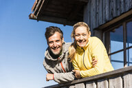 Couple leaning on balcony of a mountain hut, smiling - UUF15959