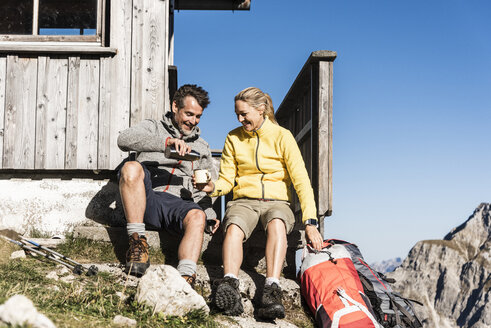 Hiking couple sitting in front of mountain hut, taking a break - UUF15962