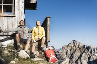 Hiking couple sitting in front of mountain hut, taking a break - UUF15965