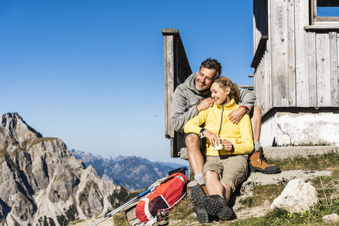 Hiking couple sitting in front of mountain hut, taking a break - UUF15968