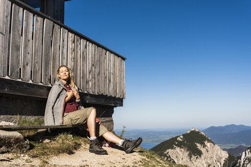 Woman relaxing at a mountain hut, enjoying the sun - UUF15983