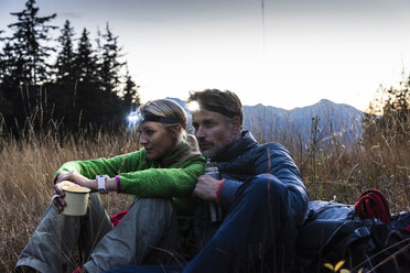 Hiking couple taking a break in the evening, wearing head lamps, drinking tea - UUF16043