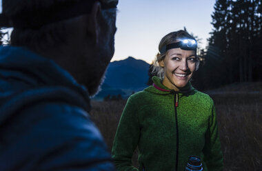 Couple hiking at night, wearing head lamps - UUF16049