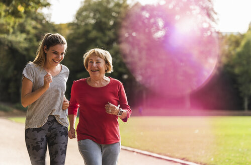 Granddaughter and grandmother having fun, jogging together in the park - UUF16055