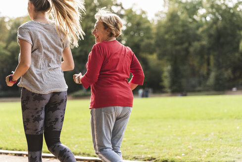 Granddaughter and grandmother having fun, jogging together in the park - UUF16058