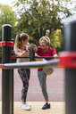 Grandmother and granddaughter training on bars in a park - UUF16067