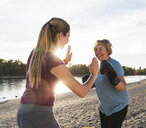 Grandmother doing boxing training with her graddaughter at the river - UUF16097