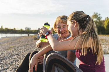 Grandmother and granddaughter taking a break after exercising at the river - UUF16103