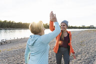 Grandmother and granddaughter high-fiving after training at the river - UUF16112