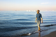 Young man walking at the beach in the evening - PUF01344