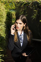 Young businesswoman talking on cell phone surrounded by plants - VABF01989