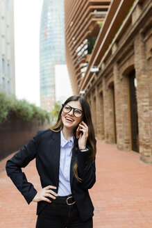 Happy young businesswoman on cell phone in the city - VABF02004