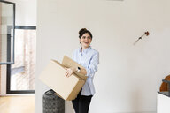 Smiling young woman carrying cardboard box in new apartment - VABF02013